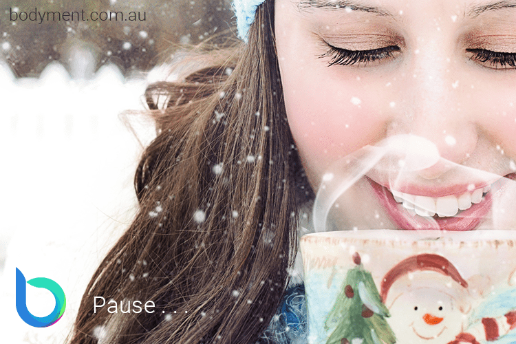 Smiling lady sipping a hot drink from a cup with a snowman on it as snow falls gently around her.